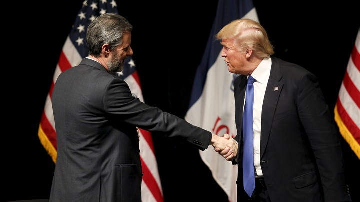 Falwell, left, smiles as he shakes hands with Trump, who appears to be mid-sentence.