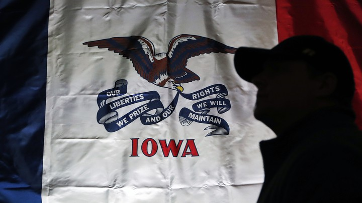 The Iowa state flag hangs at a rally site at the University of Iowa in Iowa City. A person, in shadow and wearing a baseball cap, stands in front of it.