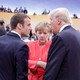 French President Emmanuel Macron, German Chancellor Angela Merkel and U.S. President Trump talk with one another.