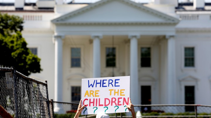 """A protester holding a sign that reads """"Where are the children?"""" in front of the White House."""