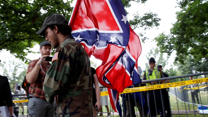 Man in fatigues carrying Confederate flag