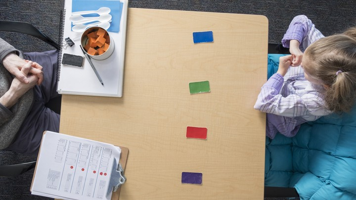 A child and an examiner sit at a table that includes colored blocks, a clipboard, and plastic spoons.