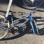 A bike missing its front wheel lies in a rack at Oakland's Fruitvale BART station.