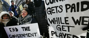 Government workers and their supporters hold signs during a protest in Boston.