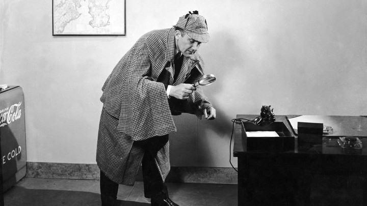 A detective looks through a magnifying glass.