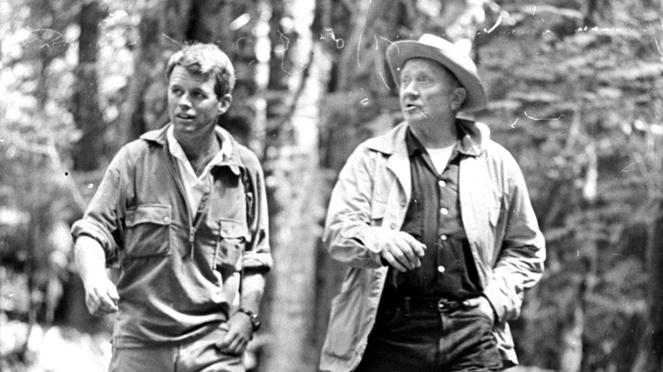 Robert F. Kennedy and Supreme Court Justice William O. Douglas hiking through the woods wearing outdoors gear.
