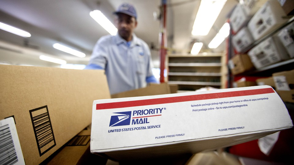 A mailman carrying several USPS packages