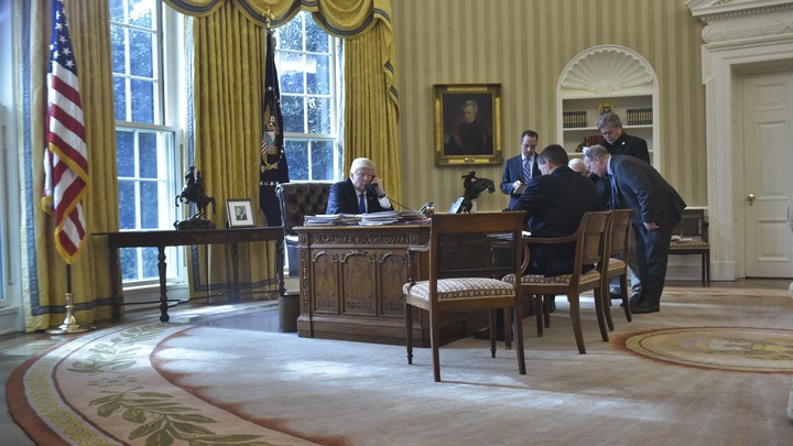President Donald Trump speaks on the phone from the Oval Office as staffers look on.