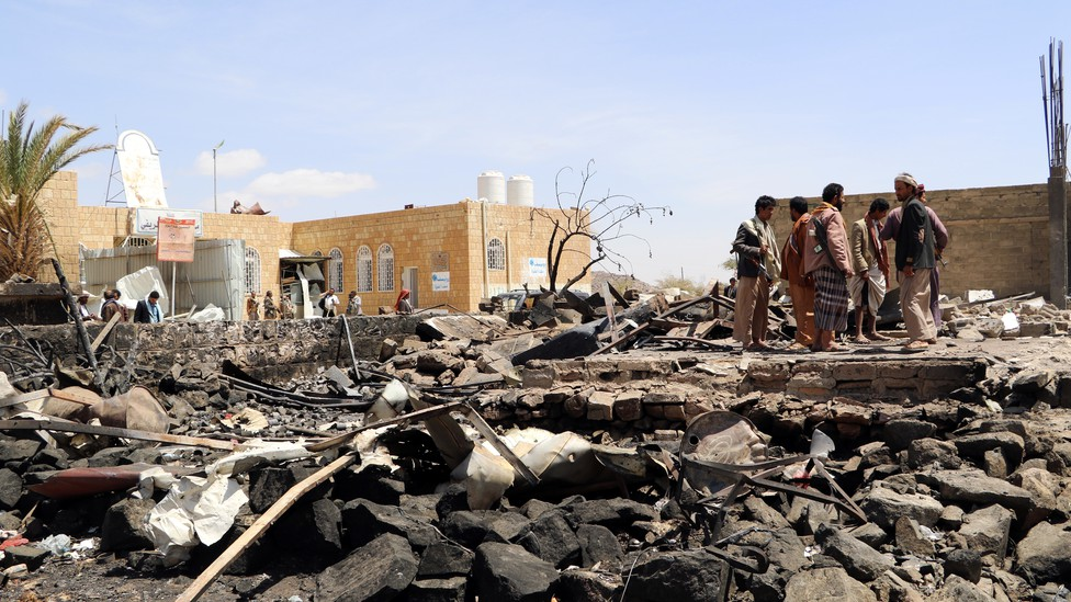 People stand at the scene of an air strike in Saada, Yemen on March 28, 2019.