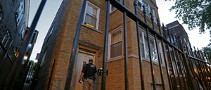 A sheriff in front of a housing unit, viewed through an iron fence