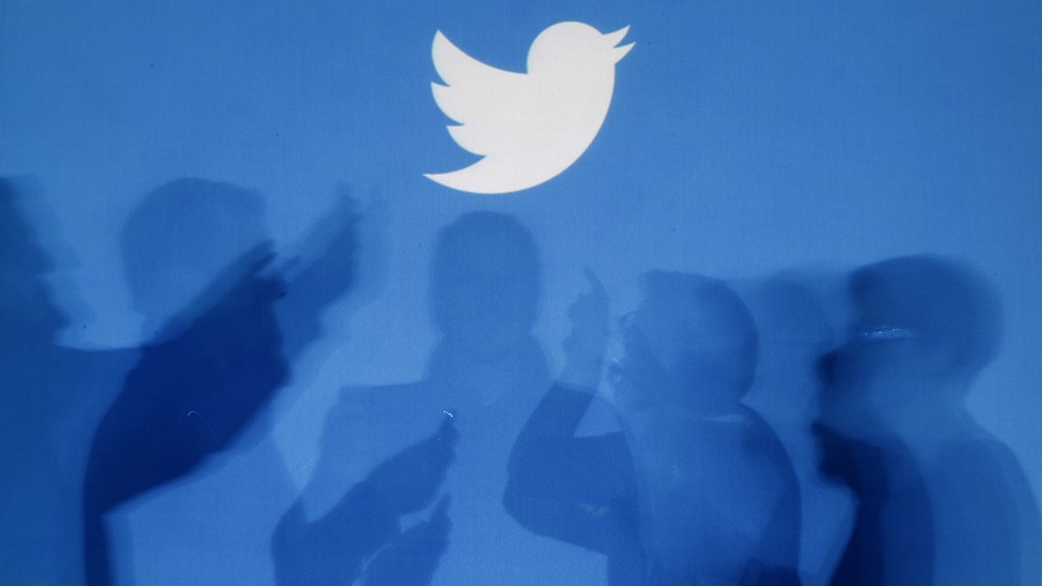 The shadows of people using smartphones against a blue backdrop with the Twitter logo