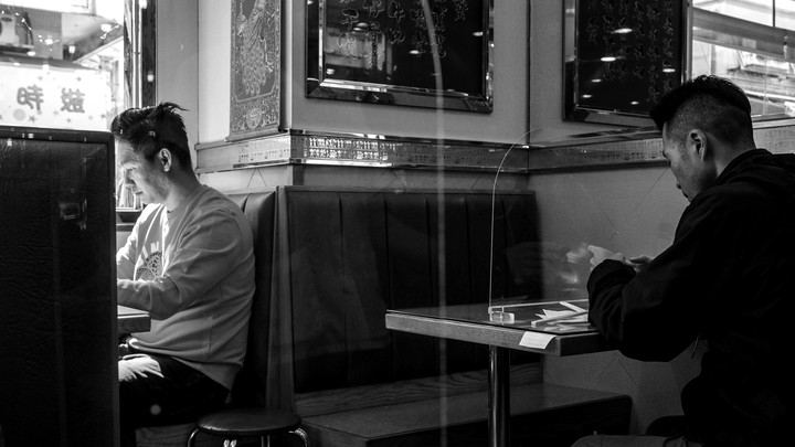 In a black and white image, people sit at different tables in a restaurant.