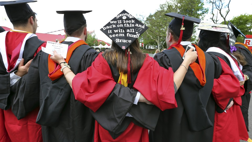 Graduates embrace in caps and gowns at commencement