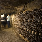 Human skulls and bones are stacked in a pile in Paris's catacombs.