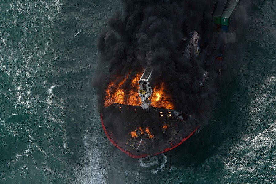 Fire and black smoke rise from a damaged ship, as seen from above.