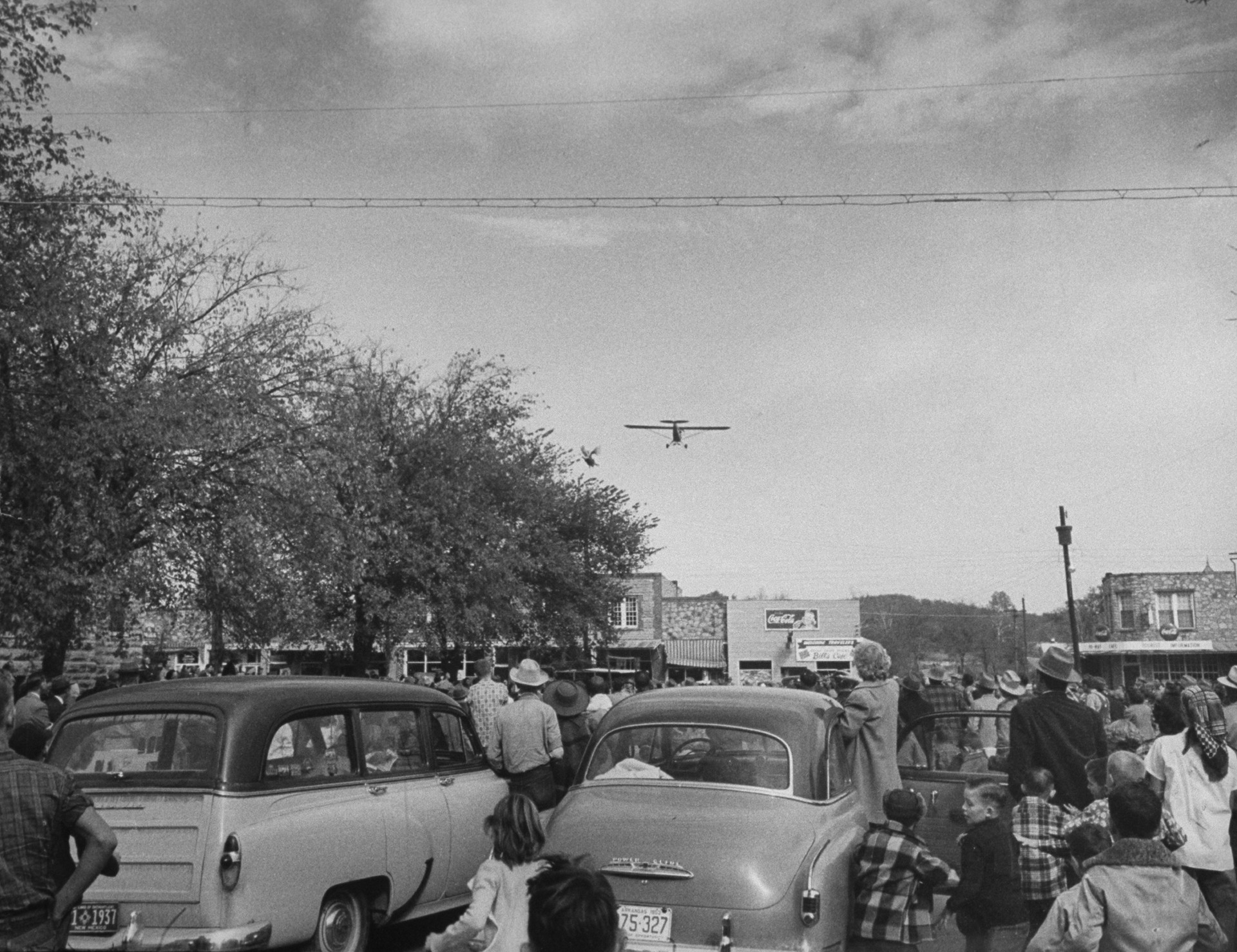 The 1953 turkey drop starts as the first bird is tossed from a low-flying plane.