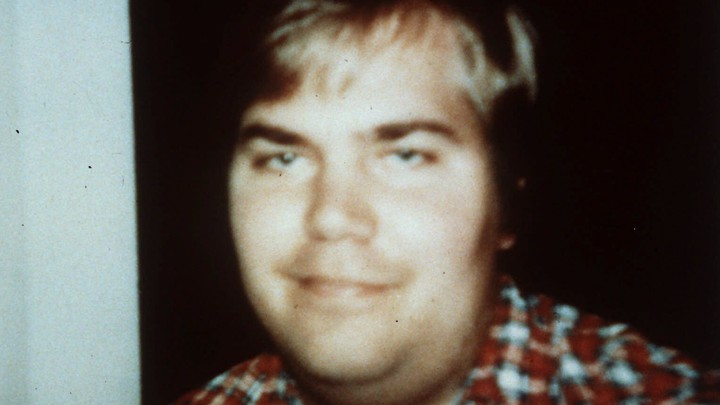 A photo of John Hinckley taken in 1999 shows him smiling and wearing a plaid shirt.