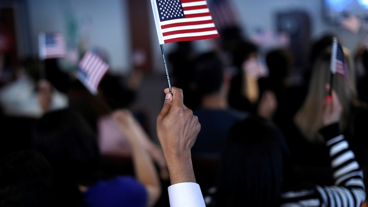 A new citizen waves an American flag during a naturalization ceremony.