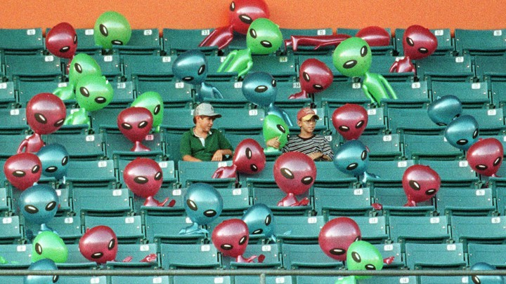 Two boys sit in a stadium surrounded by inflatable aliens
