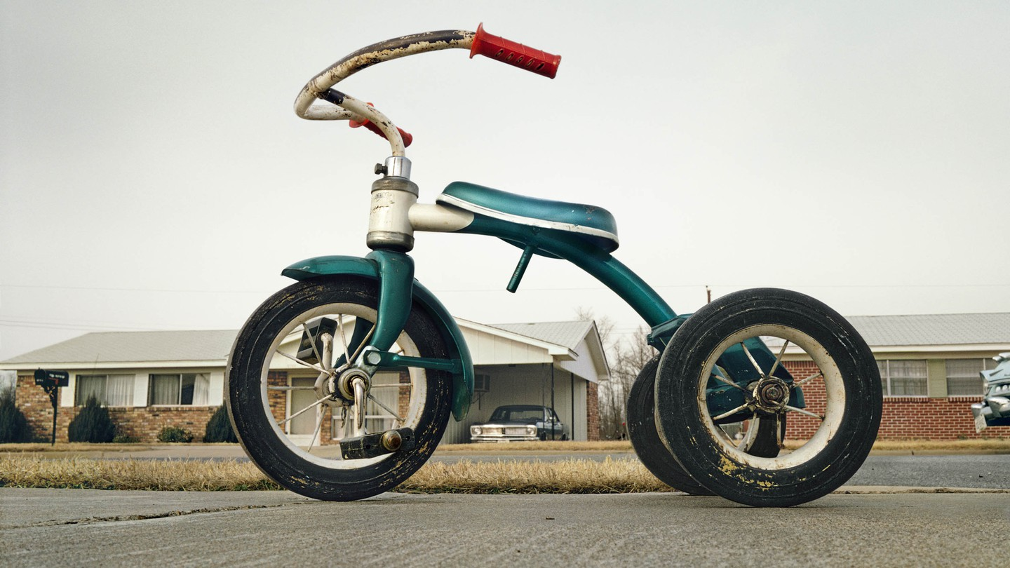A tricycle in front of a house