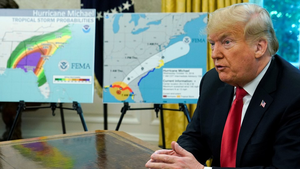 President Trump sits at a desk in front of diagrams of Hurricane Michael's path.