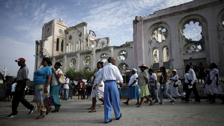 A procession walks past the ruins of the Notre-Dame de l'Assomption cathedral, destroyed in the 2010 earthquake.