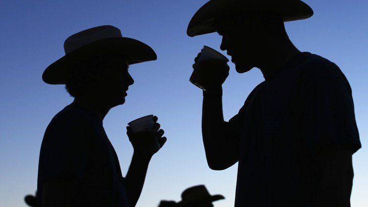 The silhouettes of two people drinking.