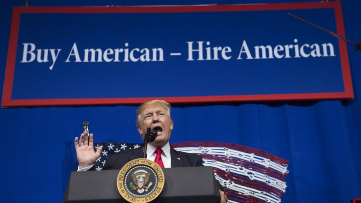"Donald Trump stands behind a podium with a banner behind him that says ""Buy American - Hire American"""
