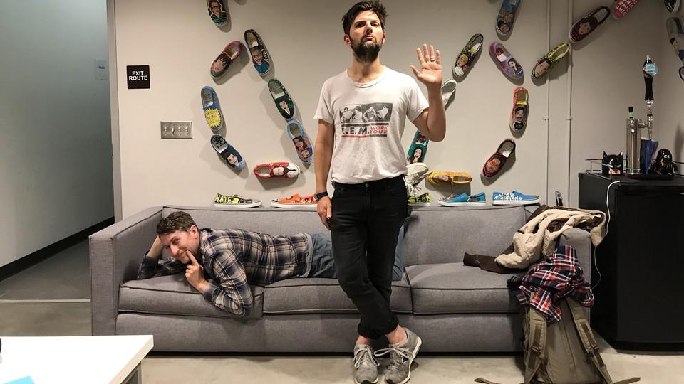Adam Scott and Scott Aukerman posing in the studio where they record the podcast 'R U Talkin' R.E.M. Re: Me?'
