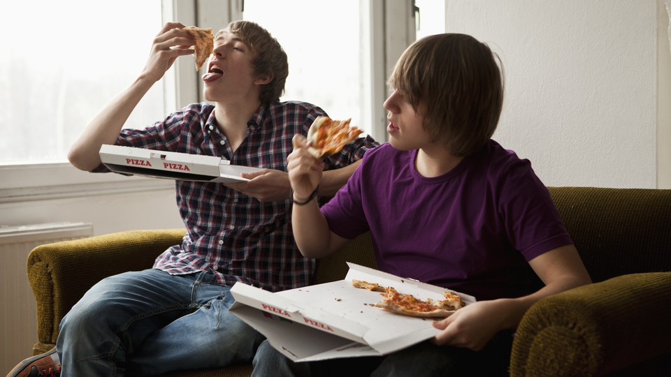 Two teenage boys eating pizza