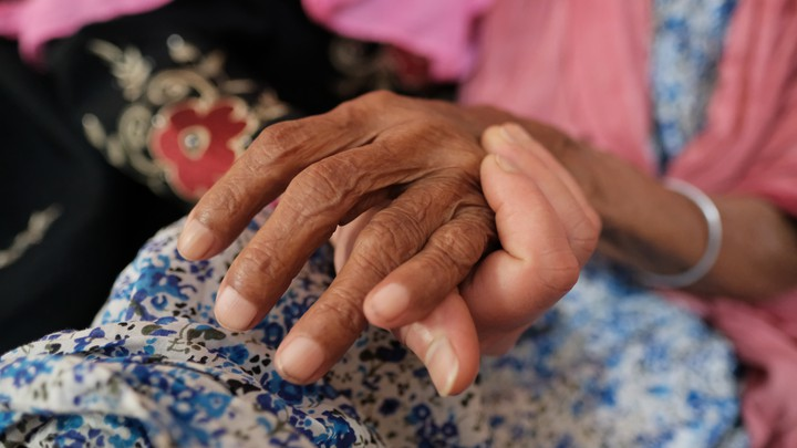young hand underneath elderly hand