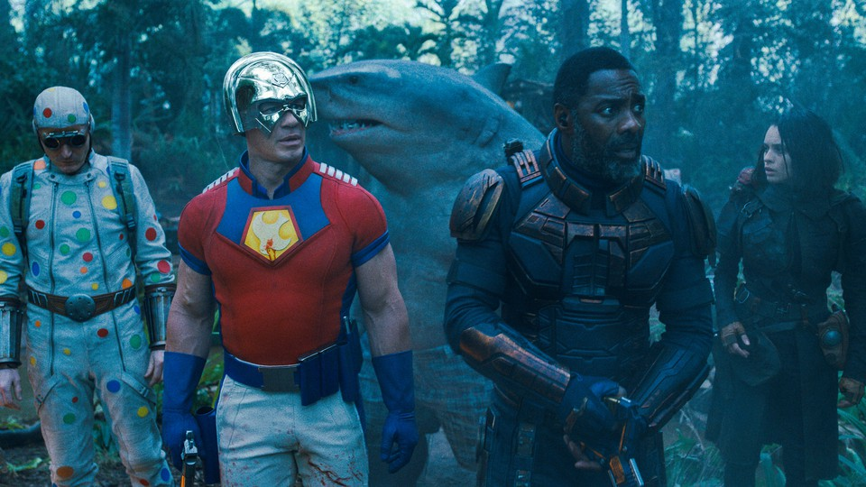"""Five characters from """"The Suicide Squad"""" stand together, facing forward. One wears a loose, gray bodysuit covered in colorful dots; another wears a silver helmet, a fitted red-and-blue T-shirt, and blue gloves; one is a human-shark hybrid; and two wear black."""