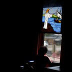 A woman stares out the window from beneath a stained-glass panel in a church