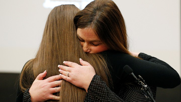 Two women embrace.