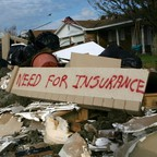 """A pile of debris with a sign reading """"need for insurance."""""""