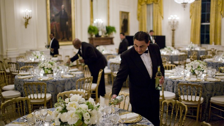 A butler pours wine before a congressional dinner at the White House.