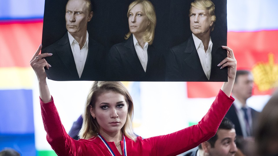 A journalist holds a picture of Vladimir Putin, Marine Le Pen, and Donald Trump at a December news conference in Moscow.