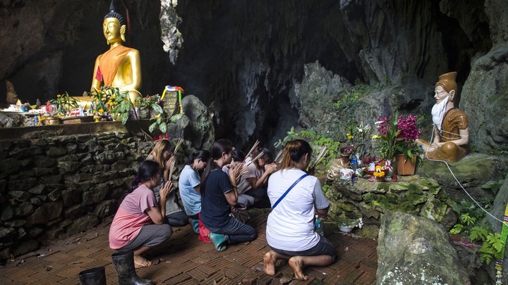 Family members pray before a shrine in Tham Luang cave area as operations were underway for the 12 boys and their coach.