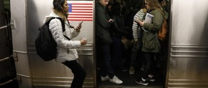 Passengers on a full subway train are pictured.