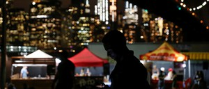 A man uses his mobile phone at night near food stalls at a festival in New York.