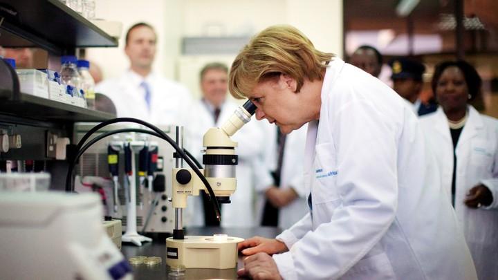 Angela Merkel looks through a microscope while wearing a white lab coat.