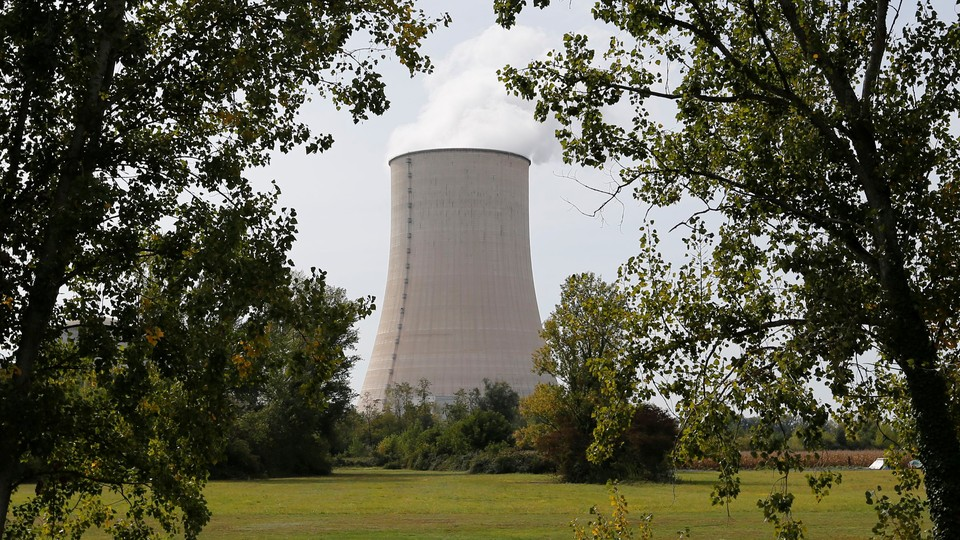 A nuclear cooling tower is framed between two trees, at the edge of a long, green field.