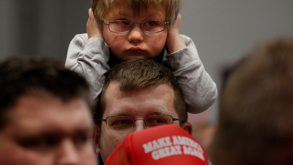 Child covers his ears during a Trump campaign rally