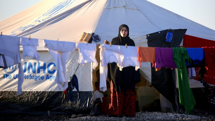 A woman hangs laundry at a refugee camp in Syria in March 2017.