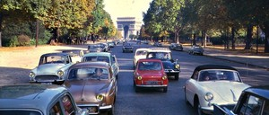 Cars drive on a tree-lined street in Paris, France, 1962.