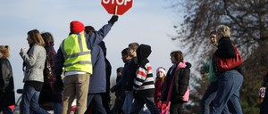 A crossing guard guides a group of elementary school students across the street.
