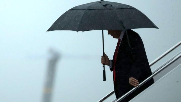 Donald Trump stands underneath an umbrella.