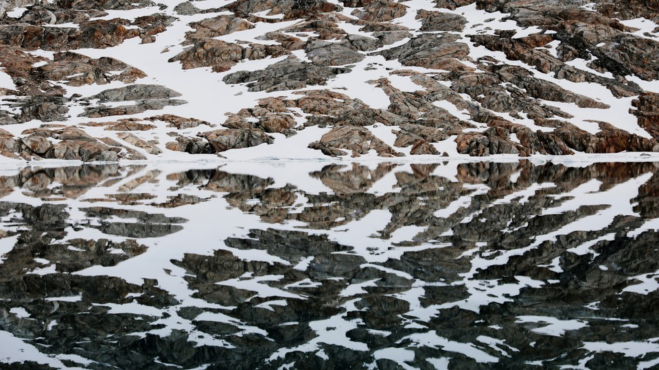 A snow-covered shore reflected in water