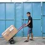 A Filipino man pushes a box in a warehouse.