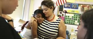Mirna Vasquez hugs her teacher, Maria Victoria Mendoza, in her classroom in Brentwood, N.Y.